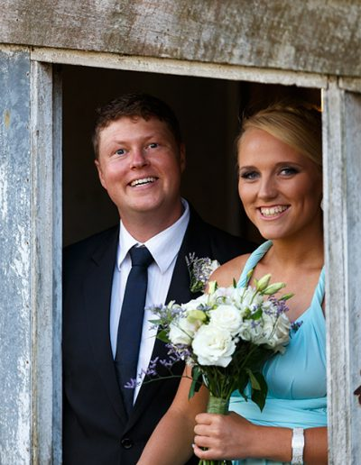 Cheeky groomsman and bridesmaid looking out the barn window
