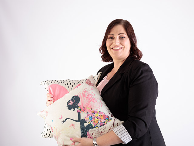 Sally from Isaac and Mai holding cushions for a corporate shoot